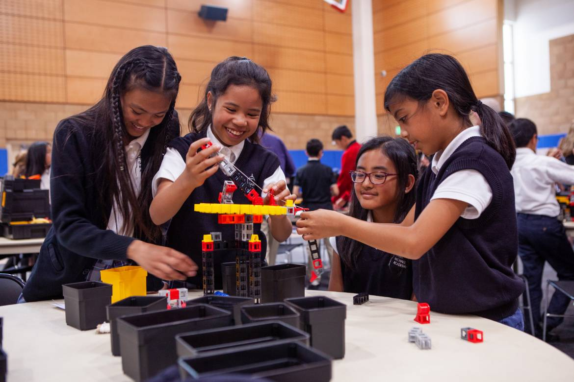 Image of a group of students enjoying building a machine from a STEM kit