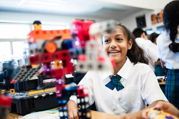 Image of smiling student looking over a machine built from a STEM Education Kit