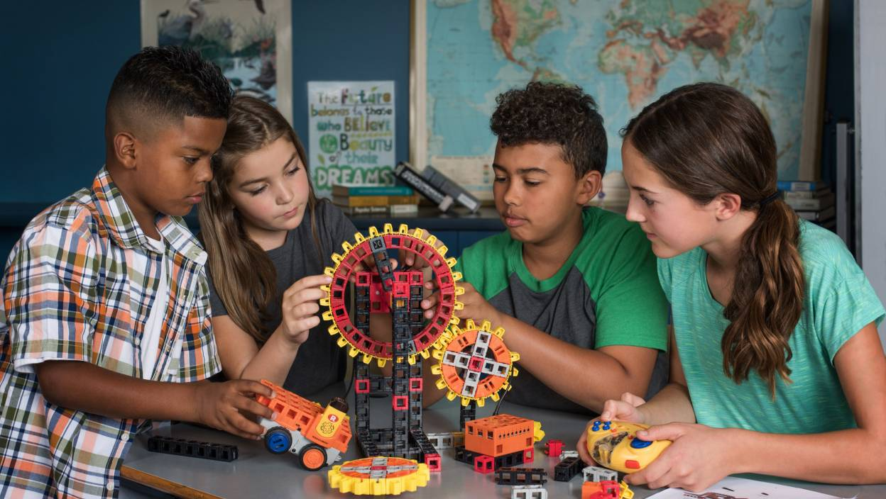 Image of kids around an Engineering Pathways Lab Kit building in middle school