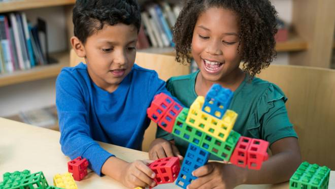 Image of two elementary school children working with blocks from a STEM education kit for Kid Spark