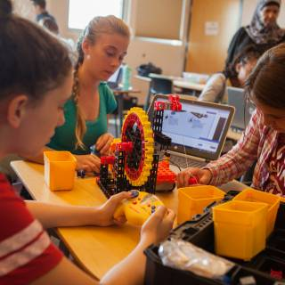 Image of kids working with a STEM education kit with computers and a mechanical wheel.